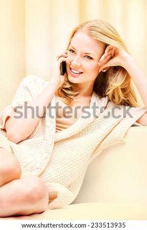 Beautiful young woman talking on the phone and smiles. She is at home.