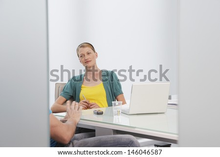 Beautiful young woman talking to cropped male colleague in office