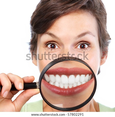 Beautiful young woman teeth and magnifying glass - stock photo