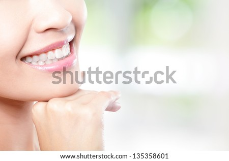 Beautiful young woman teeth close up with copy space on the right side. Isolated over green background, asian beauty model - stock photo