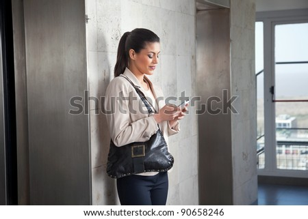 Beautiful young woman texting on cell phone - stock photo