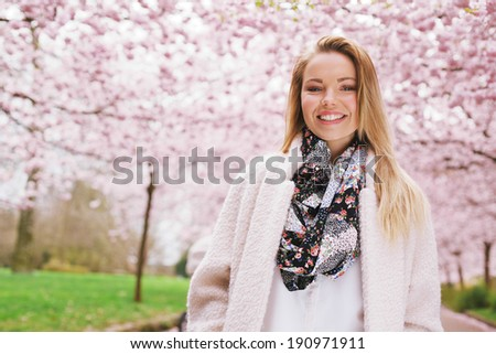 Beautiful young woman the spring blossom garden looking happy. Attractive female model standing outdoors in a park. - stock photo