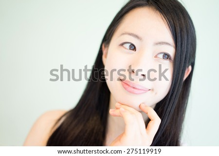 beautiful young woman thinking against light green background - stock photo