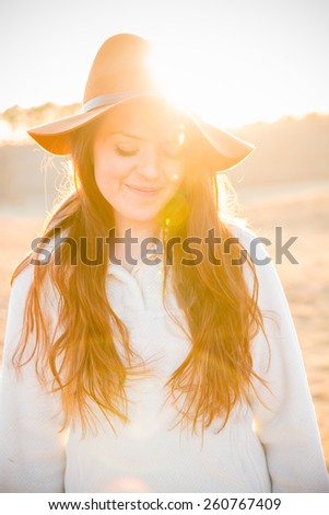 Beautiful Young Woman - This is a portrait of a beautiful young woman back lit by a sunset. Shot in a warm color tone and sun flare.  - stock photo