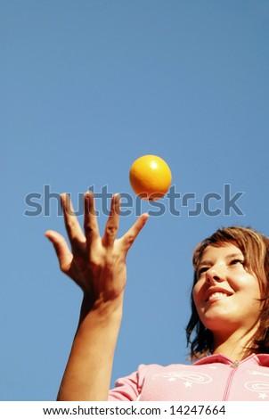 beautiful young woman throwing fresh orange in to air - stock photo