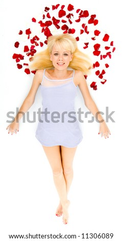 Beautiful young woman throwing rose petals against a white background