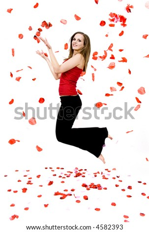 Beautiful young woman throwing rose petals against a white background - stock photo