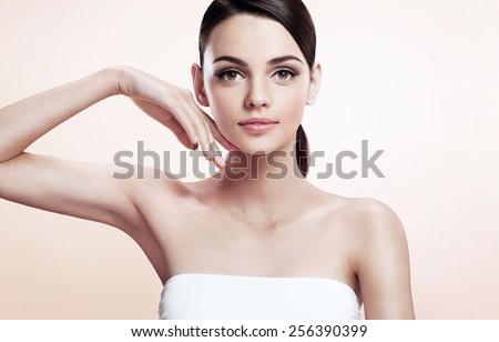Beautiful young woman touching her face, youth and skin care concept / photoset of attractive brunette girl on beige background  - stock photo