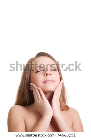 beautiful young woman touching her neck and smiling, a lot of copy space above her - stock photo