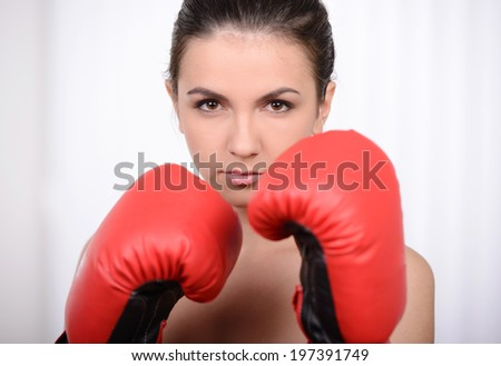 Beautiful young woman training next to a punching bag and wearing boxing gloves - stock photo