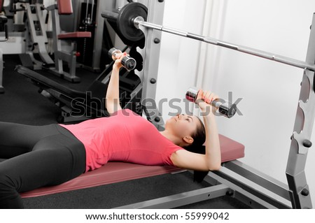 beautiful young woman training with dumbbells in a gym