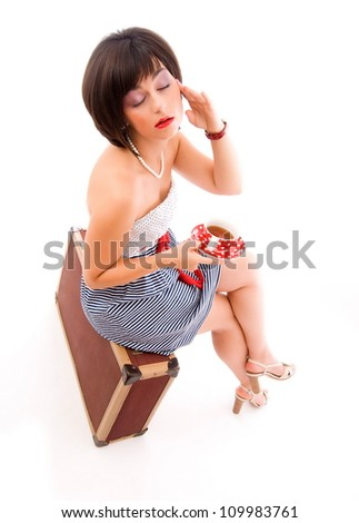 Beautiful young woman traveller with an old suitcase