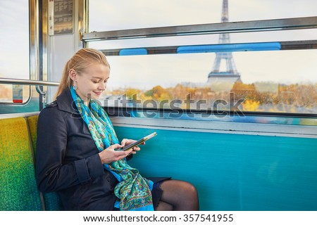Beautiful young woman travelling in a train of Parisian underground and reading a book. Eiffel tower is behind the window - stock photo
