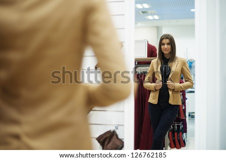 Beautiful young woman trying on jacket in front of mirror - stock photo