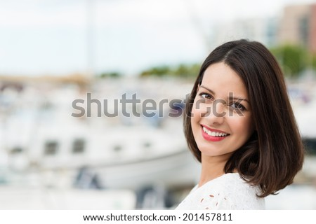 Beautiful young woman turning to smile at the camera as she enjoys a summer day at the coast overlooking a harbour, shallow dof with copyspace - stock photo