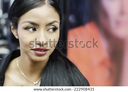 Beautiful young woman turns her head eyes wide open while she shops in mall - stock photo