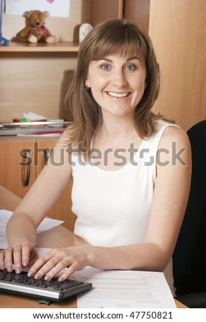 Beautiful young woman  typing on a dark keyboard with happy expression