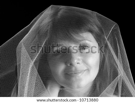 Beautiful young woman under a gauzy veil, black and white - stock photo