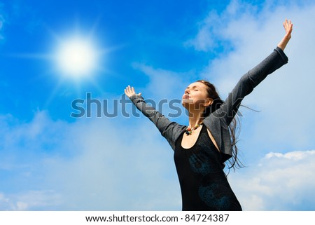 Beautiful young woman under blue sky. Portrait - stock photo
