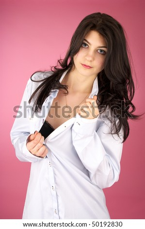 Beautiful young woman undressing over pink background - stock photo