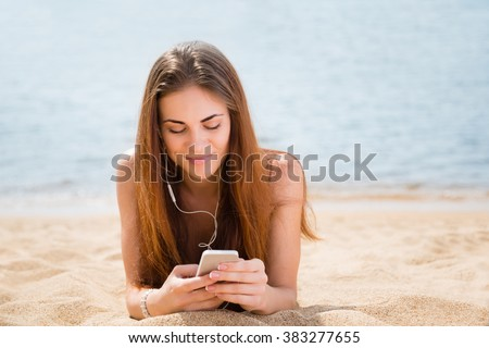 Beautiful young woman uses a smartphone, lying on the beach