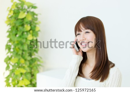 Beautiful young woman using a cellular phone - stock photo