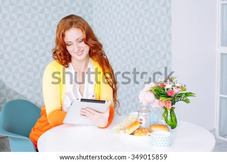 Beautiful young woman using a digital tablet in the kitchen at home