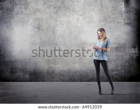 Beautiful young woman using a mobile phone - stock photo