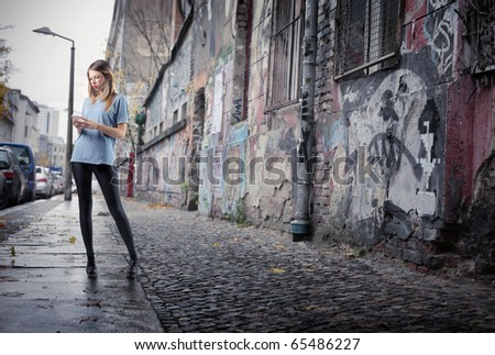 Beautiful young woman using a mobile phone on a city street full of graffiti - stock photo