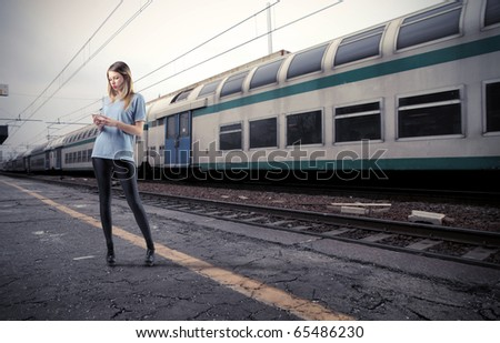 Beautiful young woman using a mobile phone on the platform of a train station - stock photo