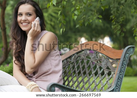Beautiful young woman using cell phone on bench in park - stock photo