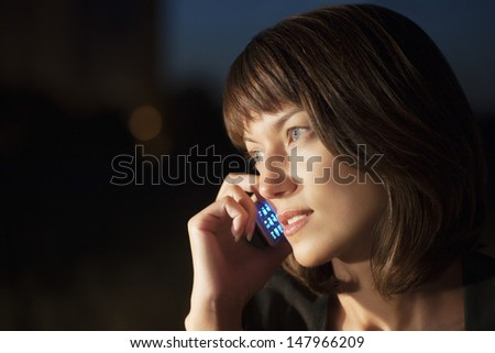 Beautiful young woman using cell phone outdoors at night - stock photo
