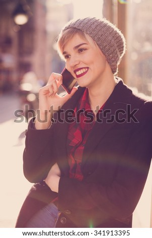 Beautiful young woman using her mobile phone on the street  - stock photo