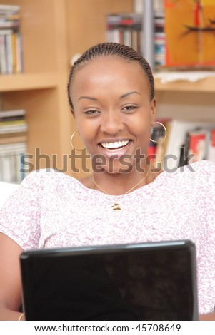 Beautiful young woman using laptop at home - stock photo