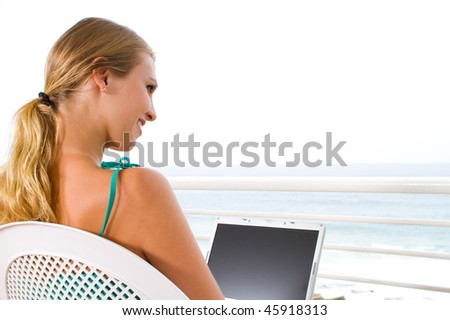 beautiful young woman using laptop on balcony with sea view behind