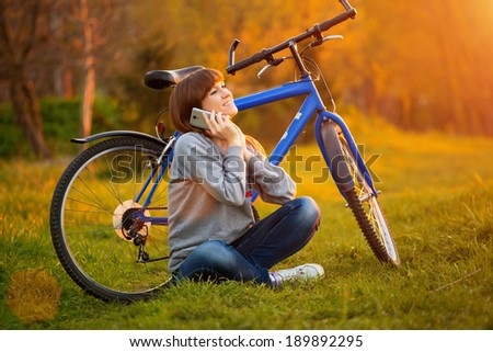 Beautiful young woman using mobile phone sitting next to her bike