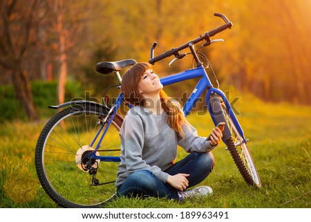 Beautiful young woman using mobile phone sitting next to her bike at sunset