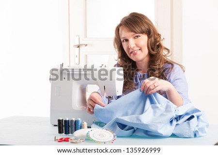 Beautiful young woman using sewing machine at home with reels of thread, pins, buttons and thimble - stock photo