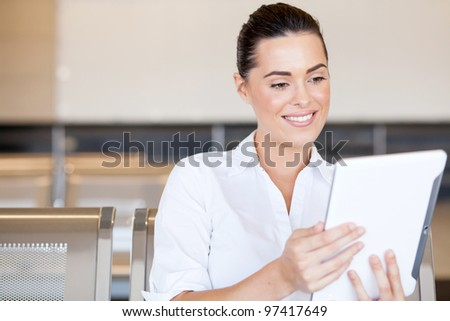 beautiful young woman using tablet computer at airport - stock photo