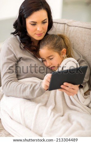 beautiful young woman using tablet computer while her daughter sleeping - stock photo