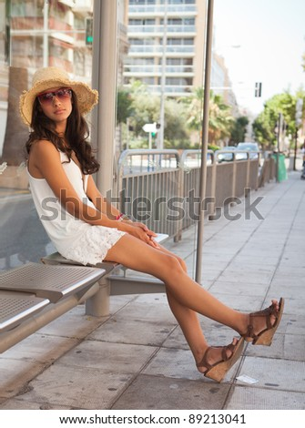 Beautiful young woman waiting for a bus in the French Riviera in Nice, France. - stock photo