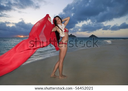 beautiful young woman walking along Lanikai Beach at sunrise with a red chiffon scarf - stock photo