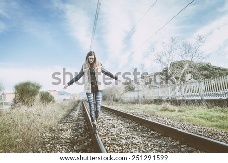 Beautiful Young Woman Walking in Balance on Railway Tracks. The Railroad is in a Residential Area. The Girl has a Casual Look. - stock photo