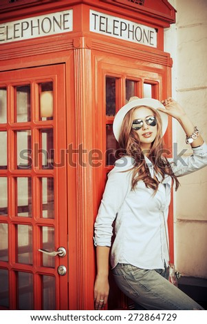 Beautiful young woman walking in the city. Europe, England. Vacation, tourist trip. Vintage style. - stock photo