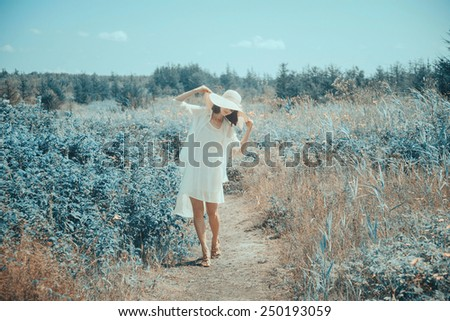 Beautiful young woman walking in wonderland - stock photo