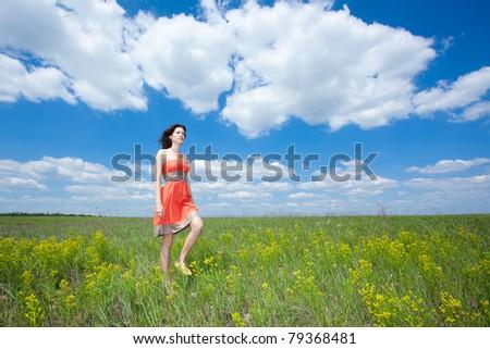 Beautiful young woman walking on field enjoying wind wave - stock photo