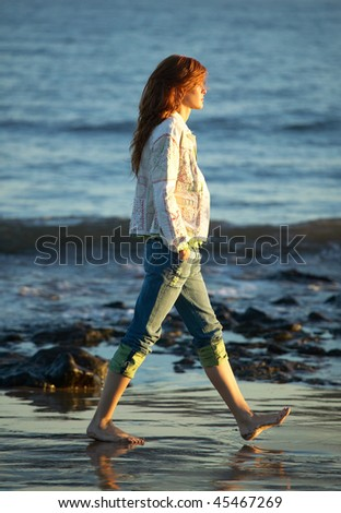 beautiful young woman walking on the beach - stock photo