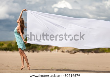 Beautiful young woman walking on the beach with a white tissue - stock photo
