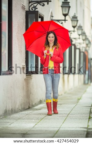 Beautiful young woman walking on the city street with red umbrella wearing red raincoat and rubber boots. She is window shopping on a rainy day. - stock photo