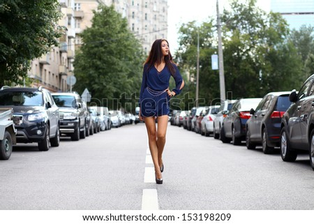 Beautiful young woman walking on the street - stock photo
